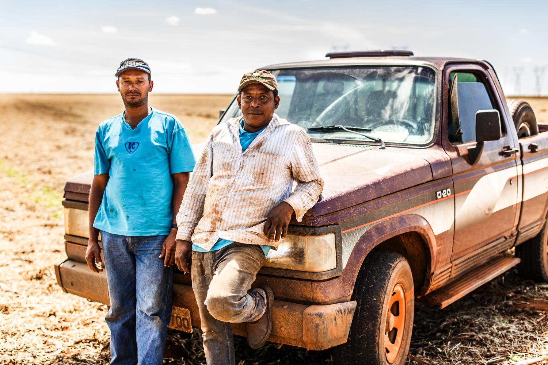 Zwei Brasilianische Arbeiter vor einem Pickup.