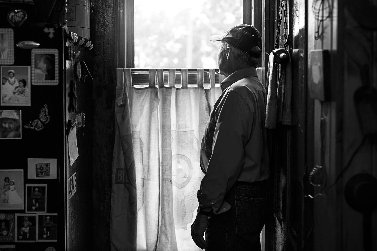 photography of a guy watching out of his window.